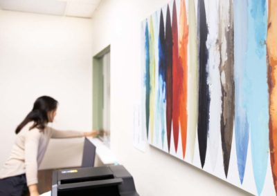 Woman hangs up wall decor in her office