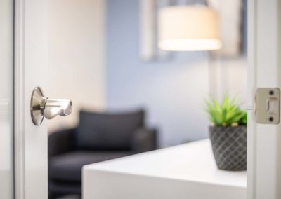 Open door into an inviting office with a couch and plant out of focus