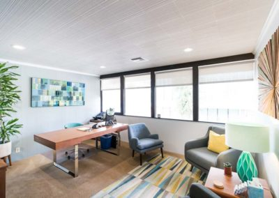 Inviting office with a desk, two cushioned chairs, and decorative teal and blue art
