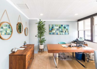 Modern office with wooden furniture, mirrors on the walls, and inviting art in the background