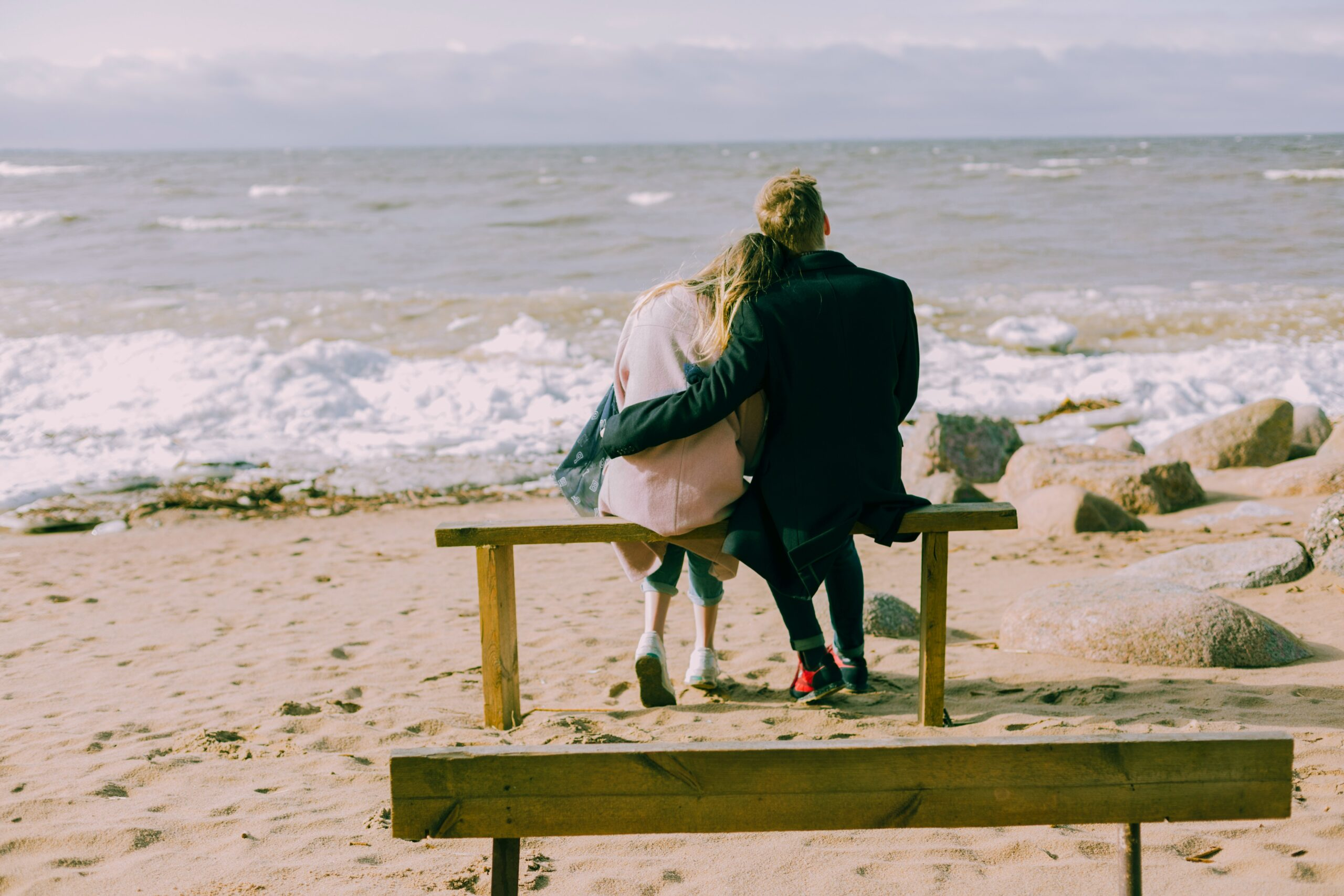 Couple sitting on a bench facing a beach